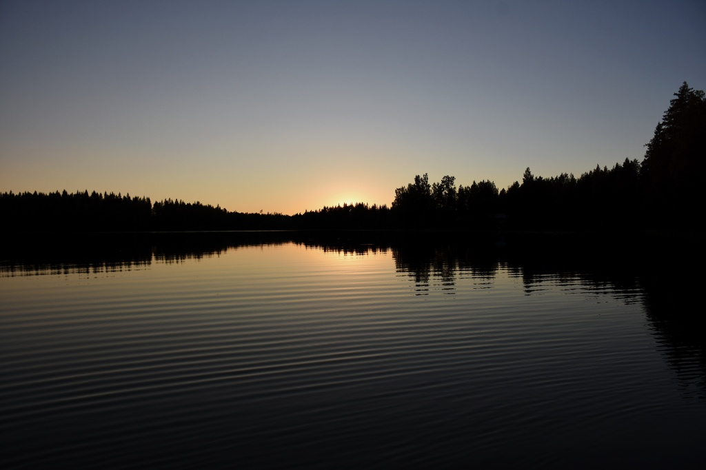 Auringonlasku ja väreilevä järven vesi