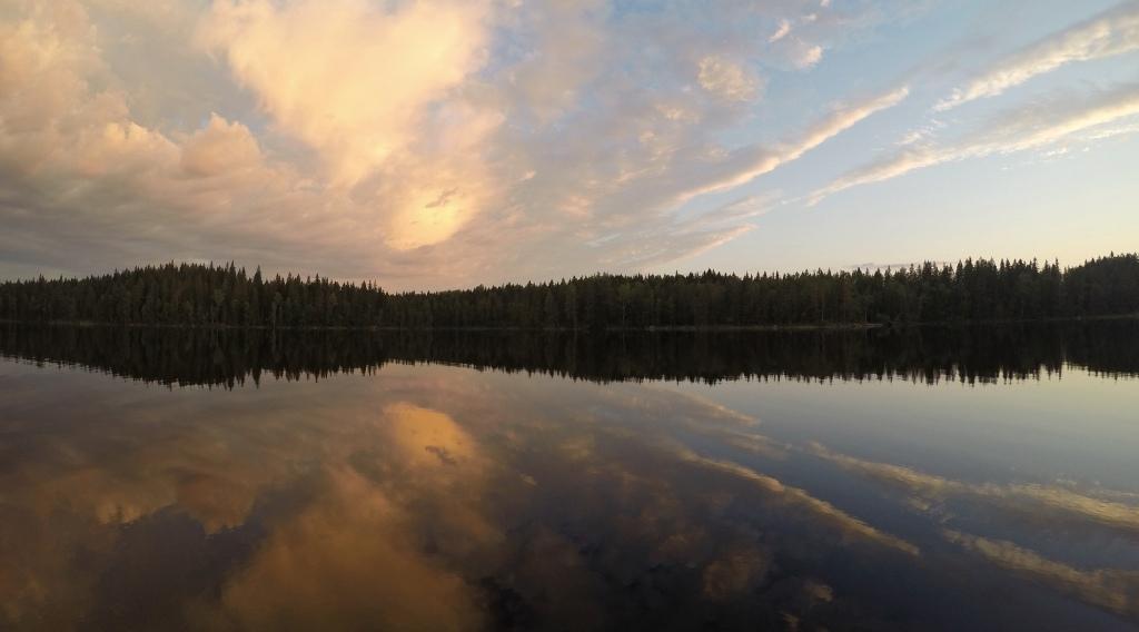 Auringonlaskun värejä peilikirkkaalla järvellä