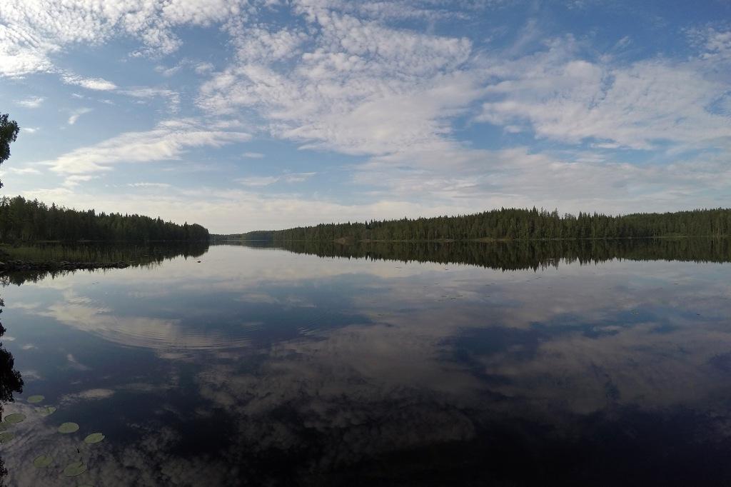 Tyyni mökkijärvi heijastaa pilvet kauniiksi pinnaltaan.